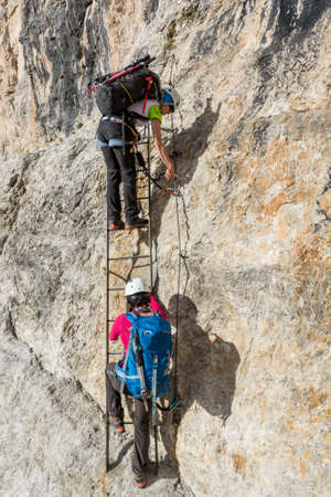 Climbers ascending metal ladder to tackle vertical wall.