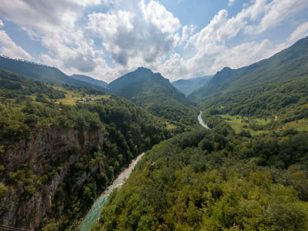 River flowing through a deep valley surrounded with forest. 写真素材