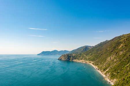 Ocean view with sun illuminating curvy coastline with hills. Cinque terre, Italy.