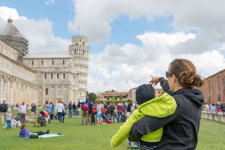 Mother carrying a child showing the Leaning tower of Pisa. Stock fotó