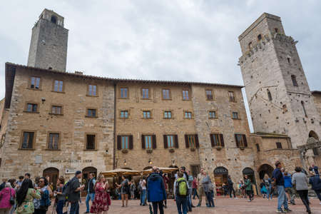 San Gimignano, Italy - May 3: Tourists exploring stony city of San Gimignano and its many towers, on May 3 2018 in San Gimignano, Italy Editöryel