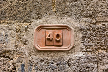 House number carved into clay tablet on facade.