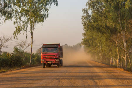 Truck speeding along dirt road across savannah and lifting large amount of dust.