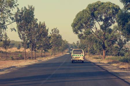 Mini bus driving along newly built road across savannah. Stock Photo - 115803558