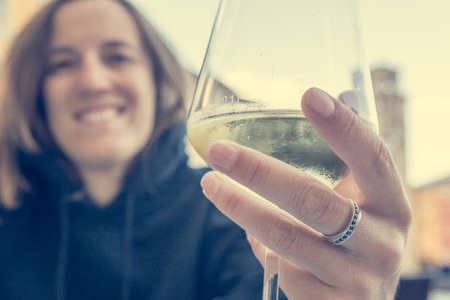 Happy woman celebrating acceptance of engagement with a glass of wine.
