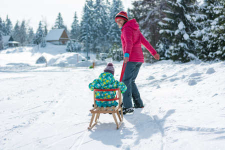 Mother pulling her daughter on wooden sledge. Stock Photo