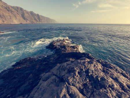 Waves splashing into volcanic coast at sunset.