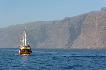 Los Gigantes, Spain - February 8: Tourist excursion ship on dolphin wathcing trip at coast of Los Gigantes, on February 8 2019 in Tenerife, Spain