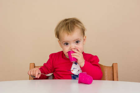 Cute blonde girl eating by herself at the table.