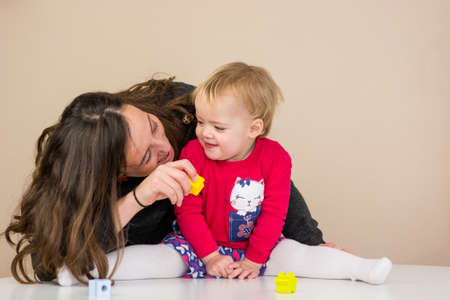 Mother playing with her daughter with wooden toys at the table.