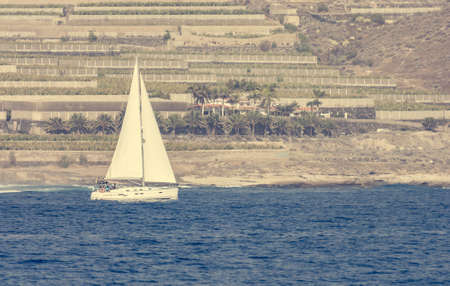 Lonely sail boat siling past terrace fields.