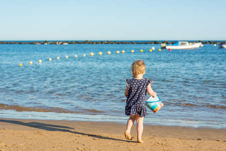 Cute little girl playing on sandy beach and exploring. Stock Photo