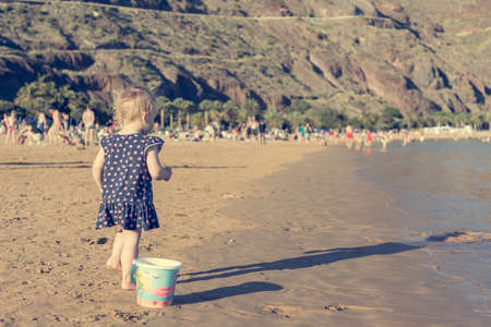 Cute little girl playing on sandy beach and exploring. Banque d'images