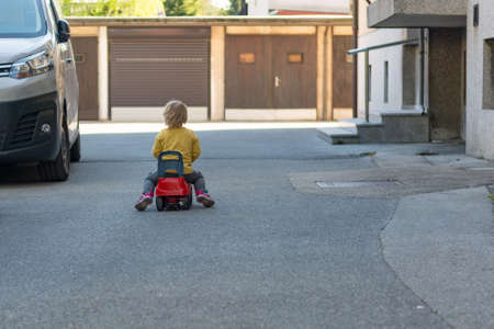 Small child playing outdoor racing her red plastic car.