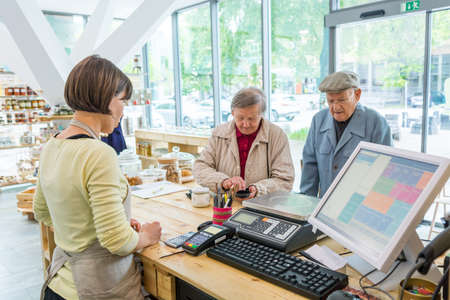 Elderly couple at cashier desk paying to teller in local zero waste store.
