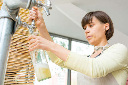 Young shopkeeper pouring delicious organic juice into glass bottle at zero waste store.