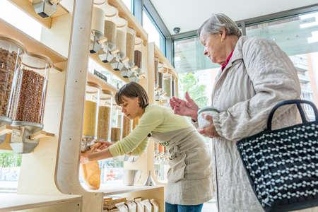 Jonge vrouwelijke winkelier helpt oudere dame in een afvalvrije winkel. Stockfoto