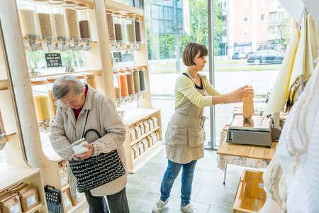 Young female shopkeeper helping elderly lady in zero waste store. 版權商用圖片