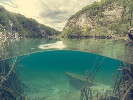 Split view of sunken boat under the lake.