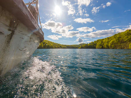 Side view of boat cruising along lake from just above the water. Plitvice national park, Croatia.