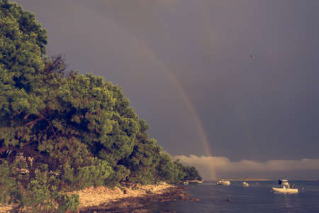 Rainbow forming across the sea after thunder storm.