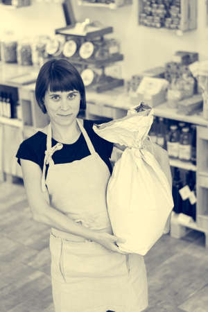 Happy female shopkeeper holding a flour bag in her arms.