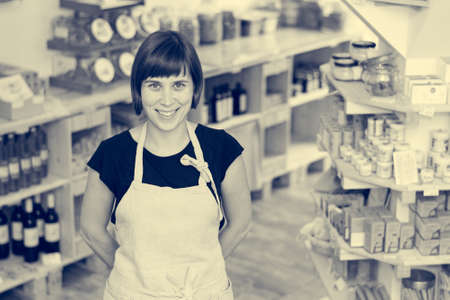 Cherfull young female shop owner posing in front of shelves full of healthy products. Stock Photo