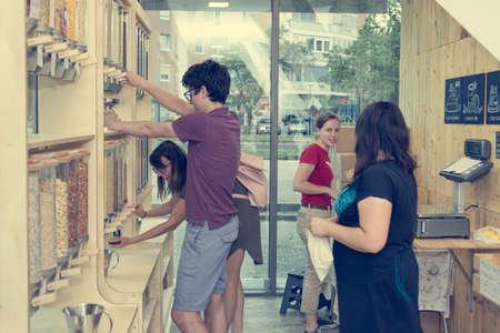 Jeunes clients caucasiens dans un magasin zéro déchet faisant leurs achats en vrac. Banque d'images