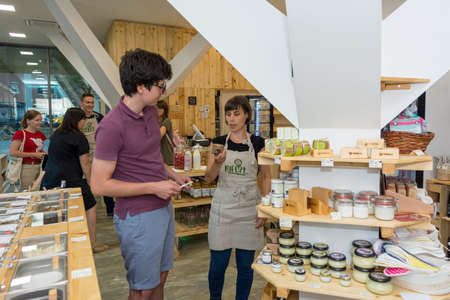 Female shop assistant helping customer decide which organic product to chose.