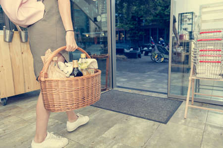 Low angle view of female walking through a grocery store door and carrying a basket full of products.