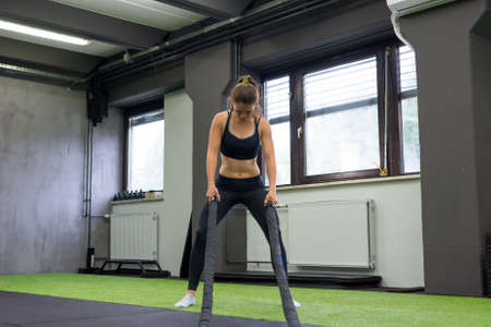 Young athletic woman exercising in gym using battle rope.