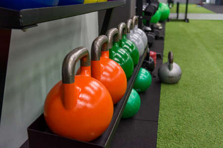 Colorful kettle bells in a row waiting for next exercise. Imagens