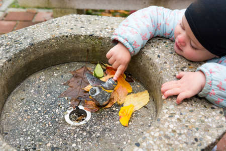 Young girl wearing a black cap exploring drinking station outdoor. Stock Photo
