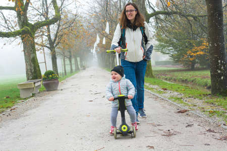 Youg mother walking with her daughter riding a toddler scooter in park. Stock Photo