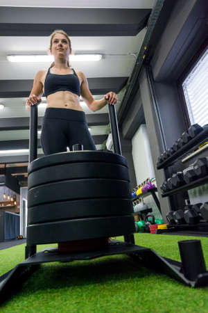 Young female fitness trainer performing sled push in local gym. Strength training front view.