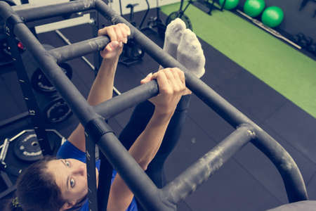 Detail of female hands gripping bar rig and doing leg raises in local gym. Banco de Imagens