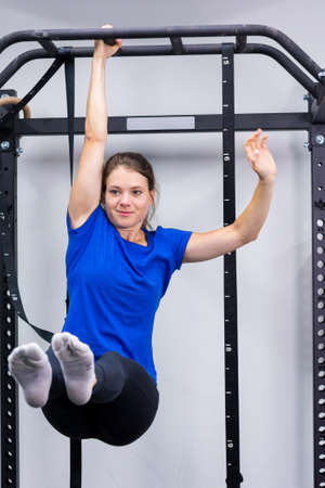 Young athletic female doing leg raises while holding with only one hand.