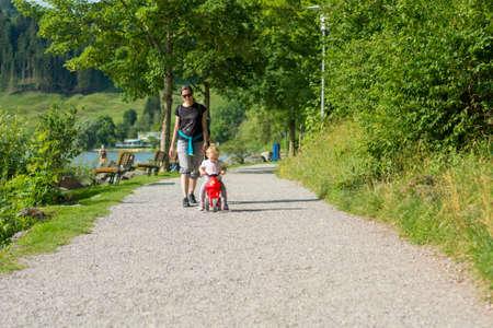 Nettes blondes Mädchen, das rotes Motorrad im Freien reitet. Standard-Bild
