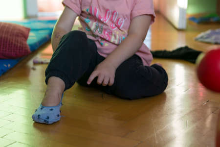 Young girl learning how to put her socks on.