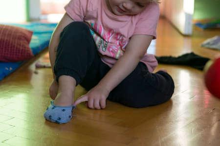 Jeune fille apprenant à mettre ses chaussettes.