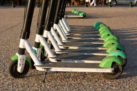 Detail of many electric scooters parked and ready to ride.