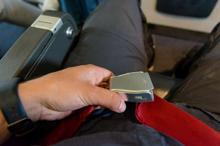 Person adjusting waist belt and getting ready for plane to take off.