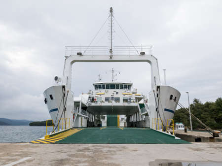 Ferry boat docked in a harbour with opened gates ready to be boarded.