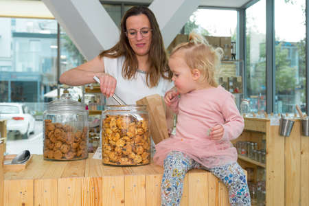 Young mother trying to fill bag with delicious cookies while her mother is eating them.