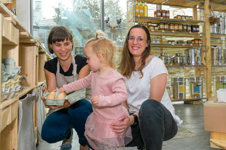 Mother and daughter picking some fresh eggs in zero waste store.