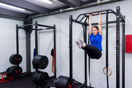 Active brunette having fun on pullup rig doing leg-raises. Imagens