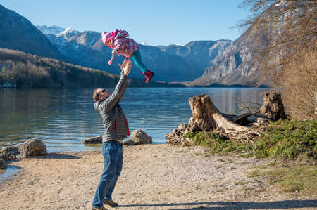 Father playing with daughter and throwing her into the air.