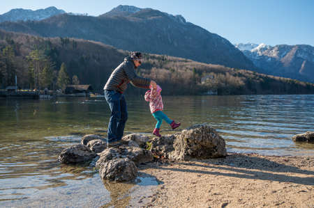 Cute girl and father walking across stones on lake.