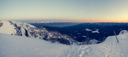 Spectacular winter mountain panoramic view of mountains at sunset.