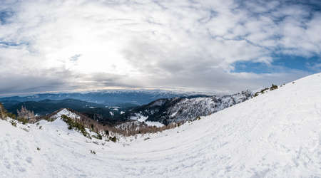 Spectacular winter mountain panoramic view of mountains with clouded sky. Imagens